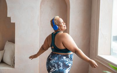 Black woman listening to headphones wearing workout clothes swaying