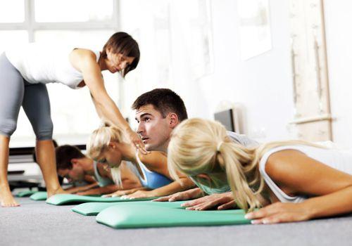 Grupo de jóvenes haciendo ejercicios de Pilates con la ayuda del instructor.