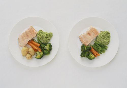 Filetes de salmón servidos con guisantes blandos y verduras al vapor en un plato y papas nuevas y verduras al vapor