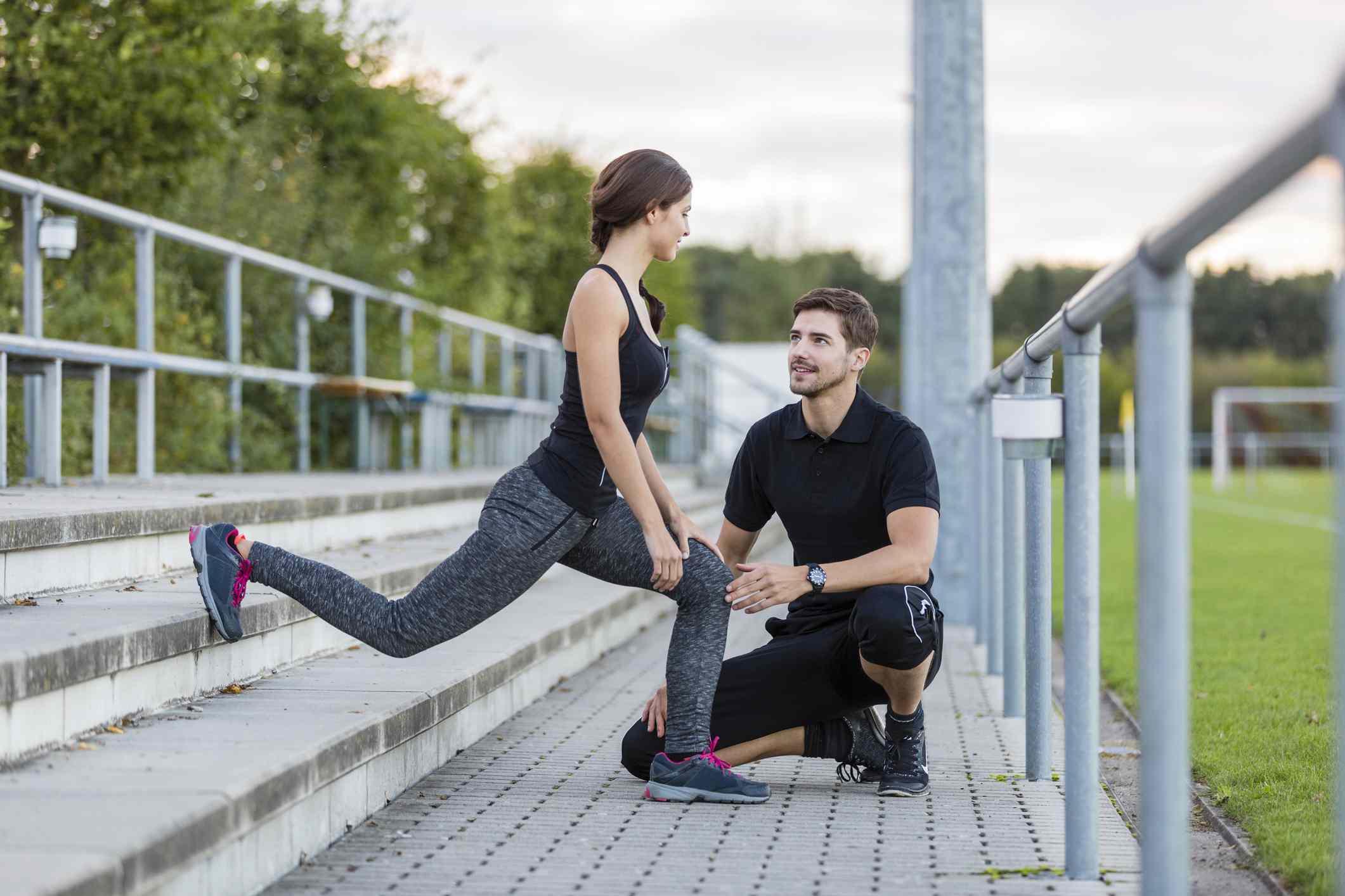 Mujer entrenando al aire libre con entrenador personal.