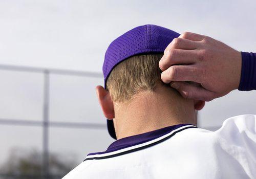 Adolescente (16-18) jugador de béisbol rascándose la cabeza