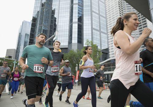 Corredores de maratón corriendo en la calle urbana