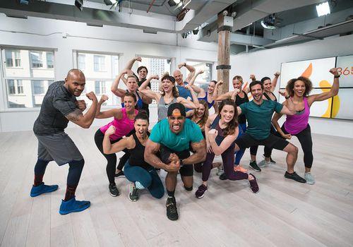 Grupo de entrenadores de Daily Burn flexionando los músculos y sonriendo