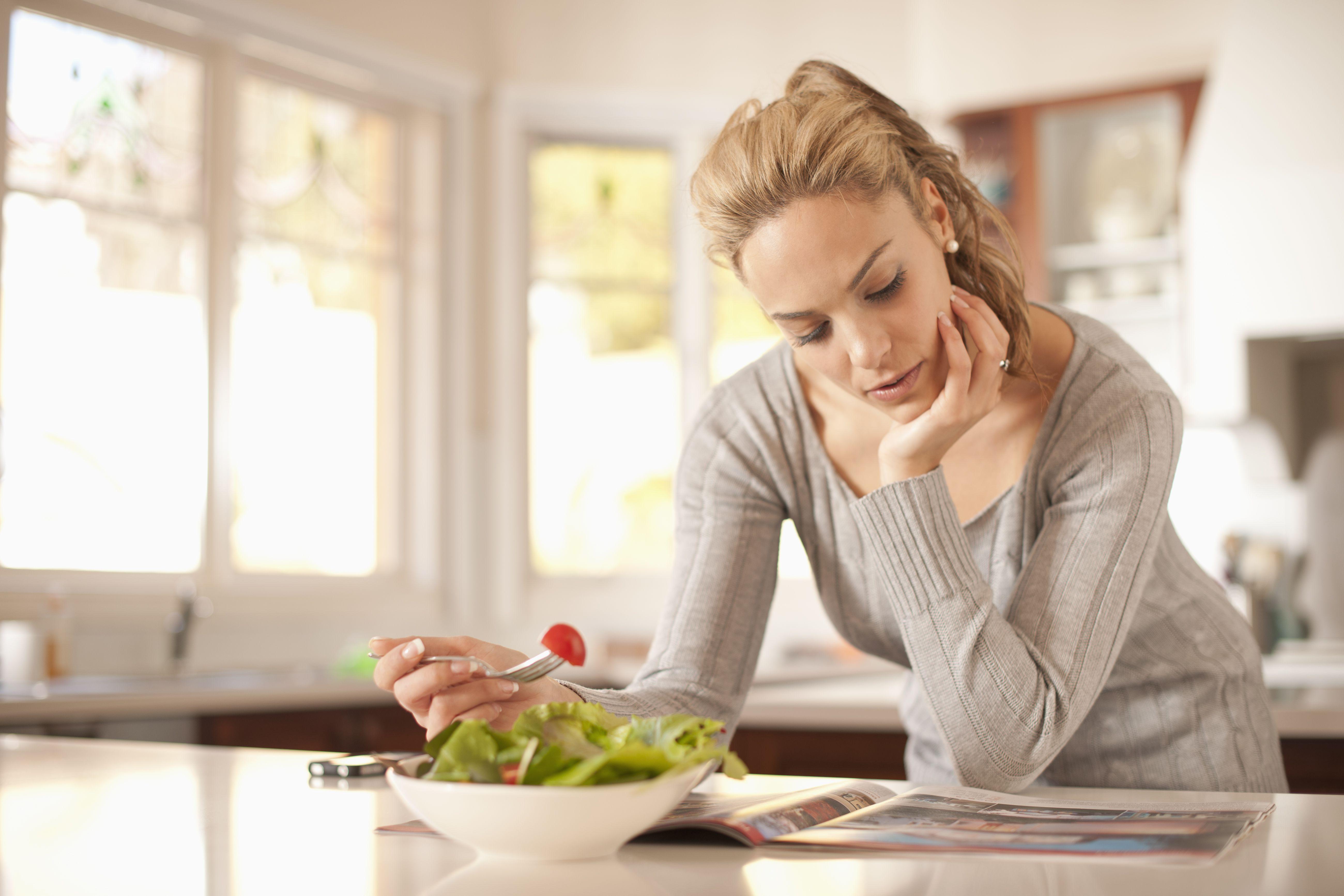 Mujer hispana, comida, ensalada, y, lectura, revista