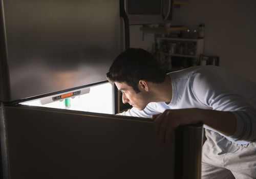 man reaching into the fridge late at night