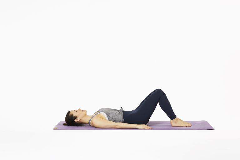 Woman lying on yoga mat imprinting in Pilates