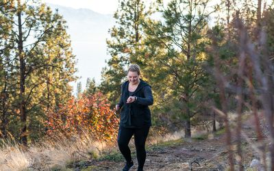 woman walking in woods and checking fitness watch