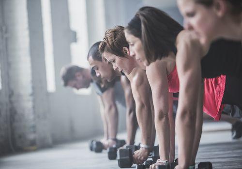 Atletas haciendo flexiones y levantando pesas en el piso