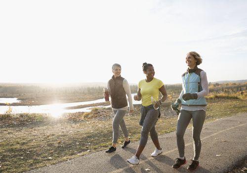 Mujeres poder caminar ejercicio en camino soleado en el parque otoño