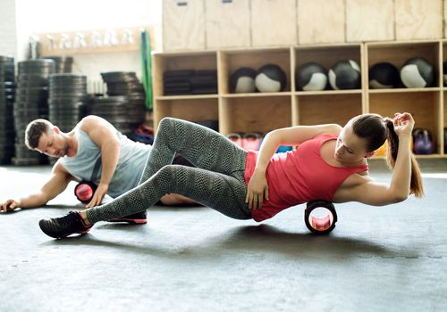Personas en el gimnasio con rodillo de soporte