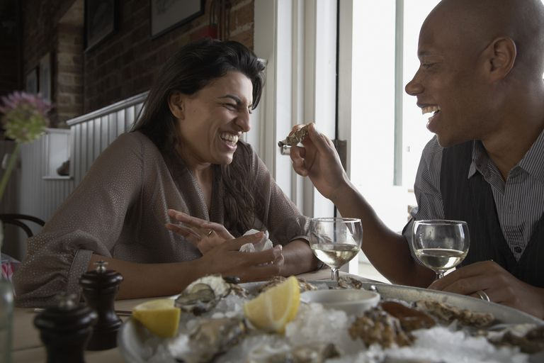 couple enjoying eating oysters together