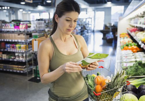 woman looking at the label on a food item in a grocery store