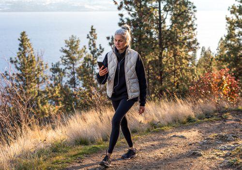Mujer caminando en el bosque y comprobar el kilometraje en el teléfono
