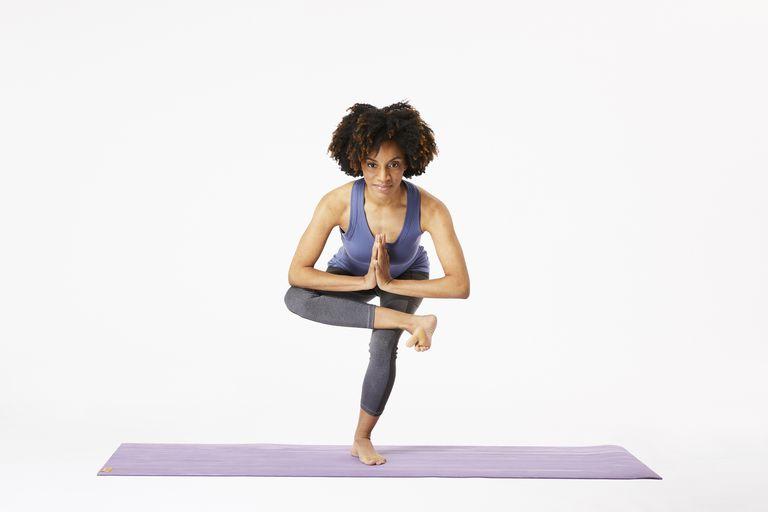 Woman on yoga mat doing one-legged chair pose