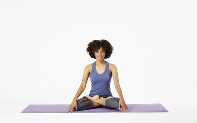 Woman sitting on yoga mat in lotus pose