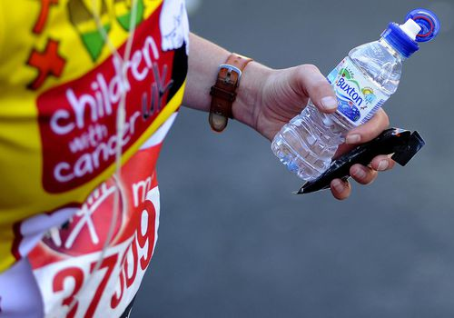A runner holds an energy bar and a bottle of water during the Virgin Money London Marathon on April 13, 2014 in London, England.