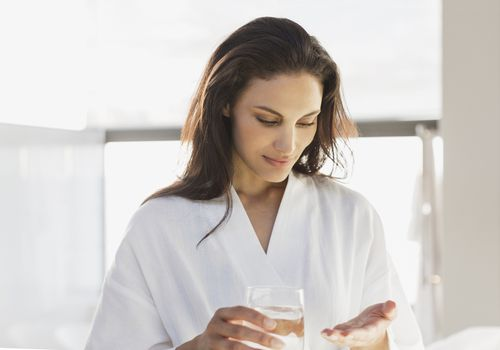 Woman in bathrobe taking medication in bathroom