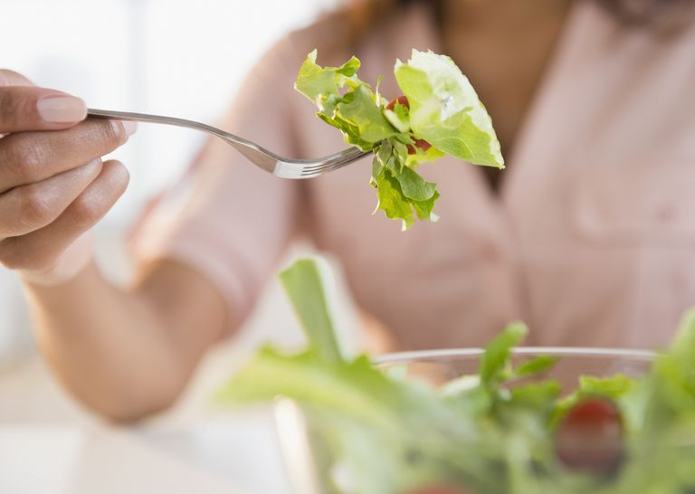 Woman eating green salad