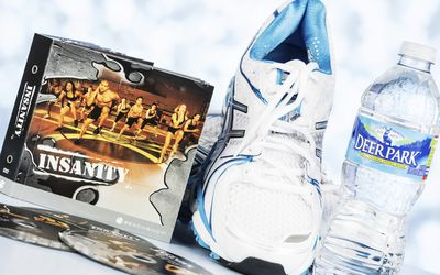 A horizontal studio shot of the intense home fitness workout program called Insanity by Beachbody. Here the DVD case and an assortment of the DVDs can be seen, along with a pair of women's Asics Gel-Kayano 18 tennis shoes and a bottle of Deer Park water.