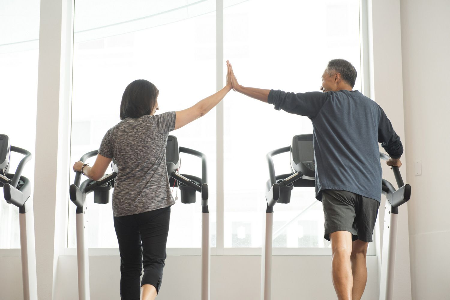 Couple high-fiving on treadmill