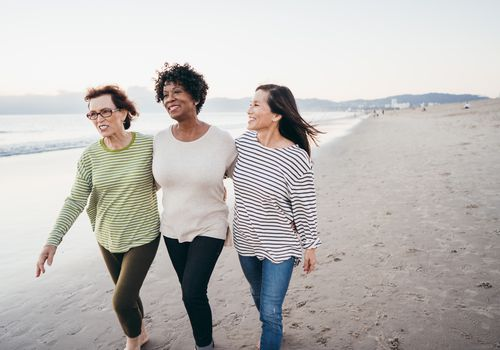 Three middle aged women walking on the beach