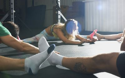 Crossfitters stretching on floor