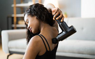 woman using massage gun on her back