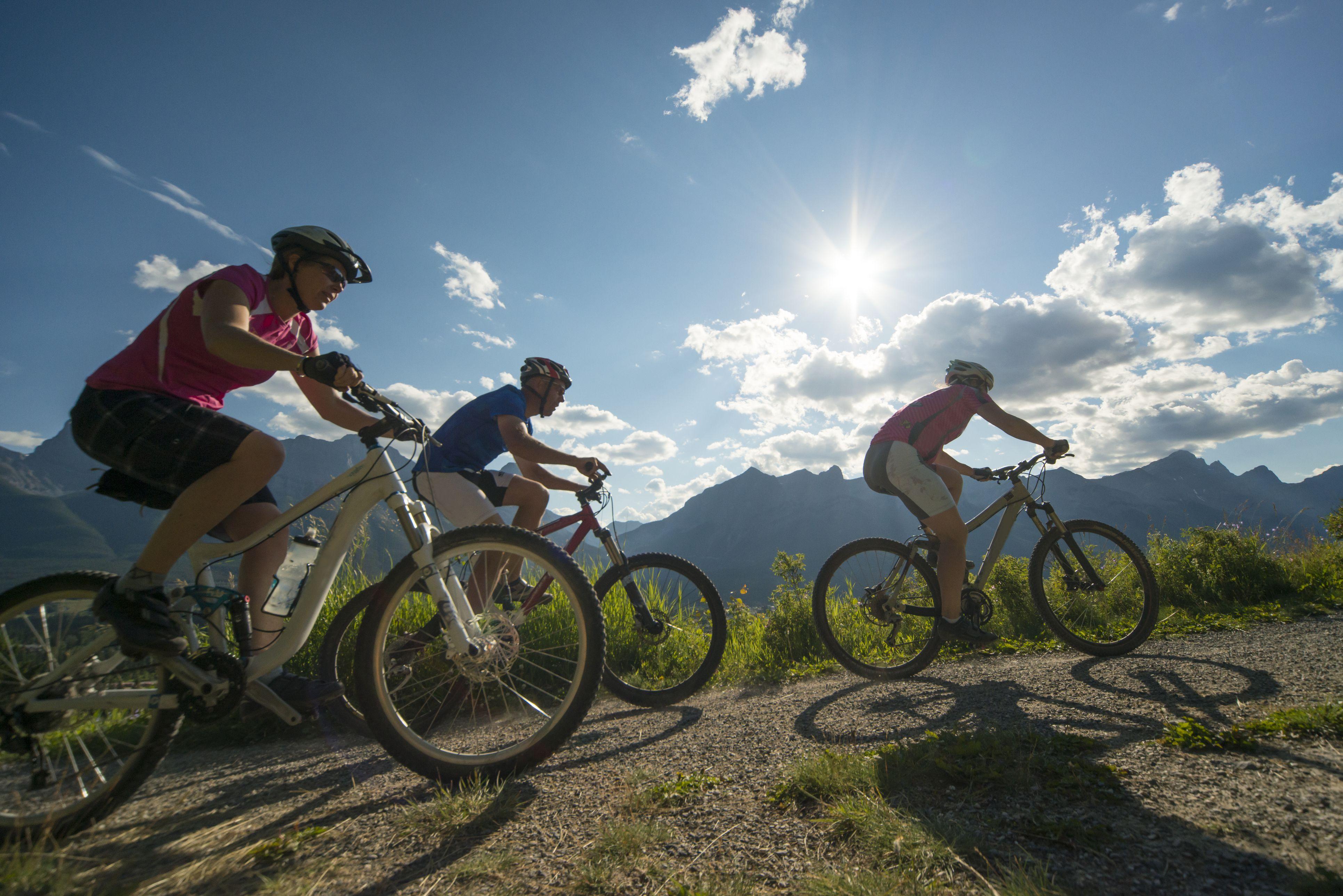 Mountain bikers race along path, in mountains