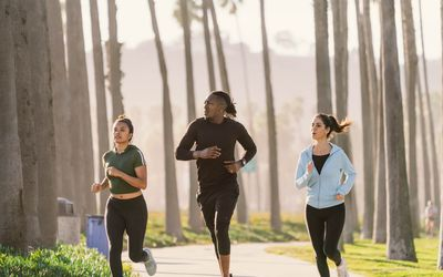 three people running together in a park