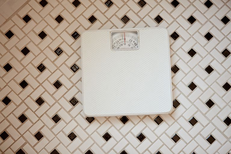 Bathroom scales on tiled floor
