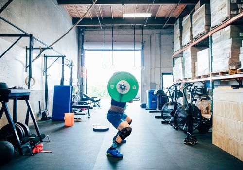 Man lifting barbell in a crossfit gym
