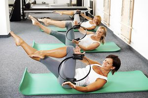 Three women sitting on the exercising mat and doing abdominal exercises with a Pilates Power Ring.