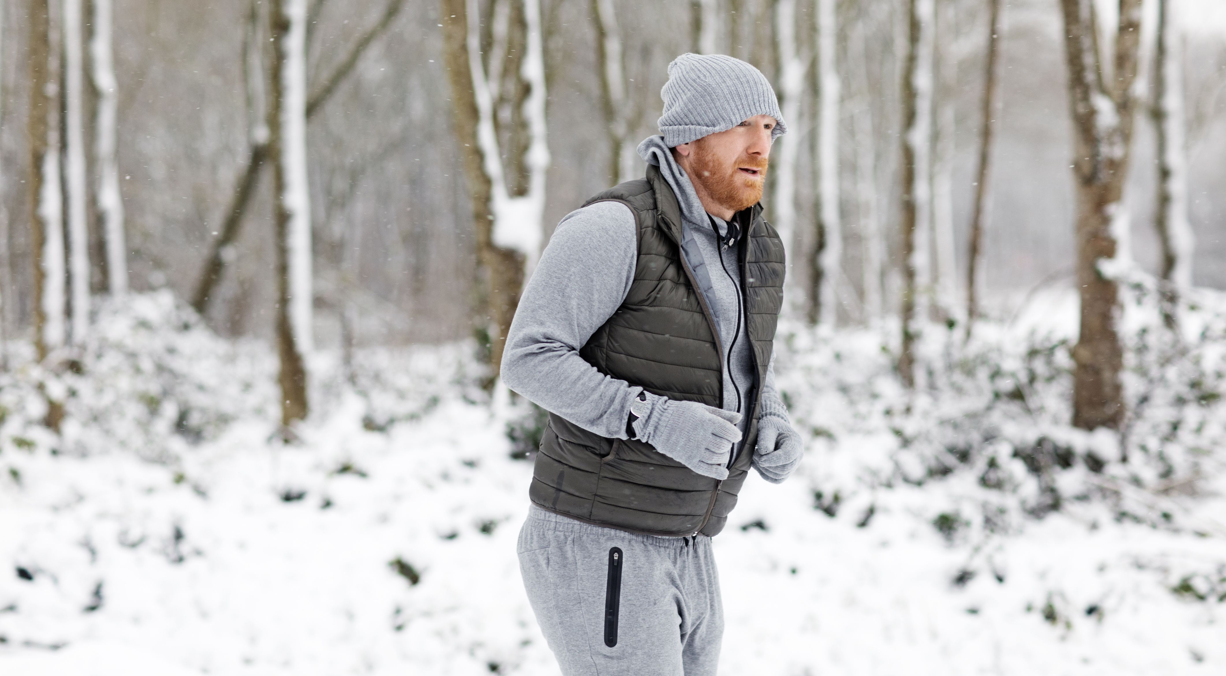 Redhead middle aged man running outdoors in the snow