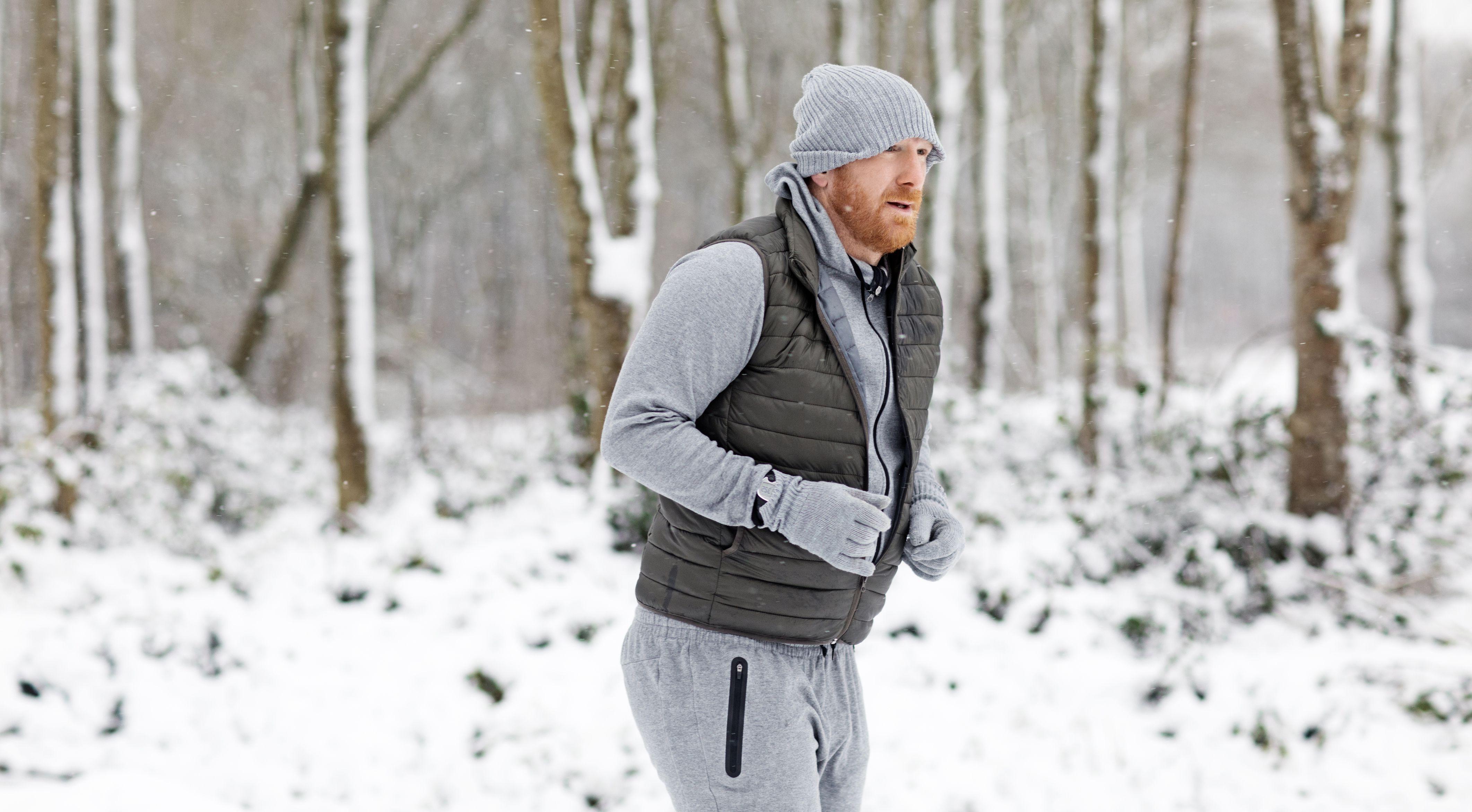 Pelirrojo hombre de mediana edad corriendo al aire libre en la nieve.