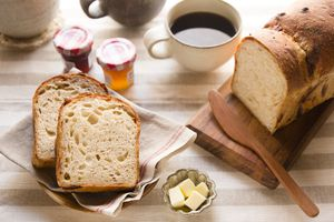 Sliced bread with coffee, butter and jam on table