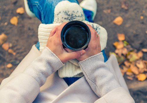 Woman holding coffee mug outdoors