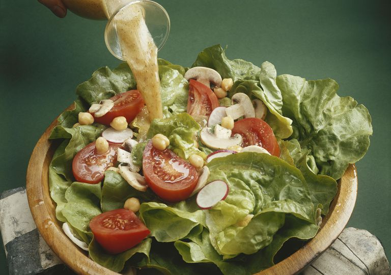 Dressing being poured on salad, close-up