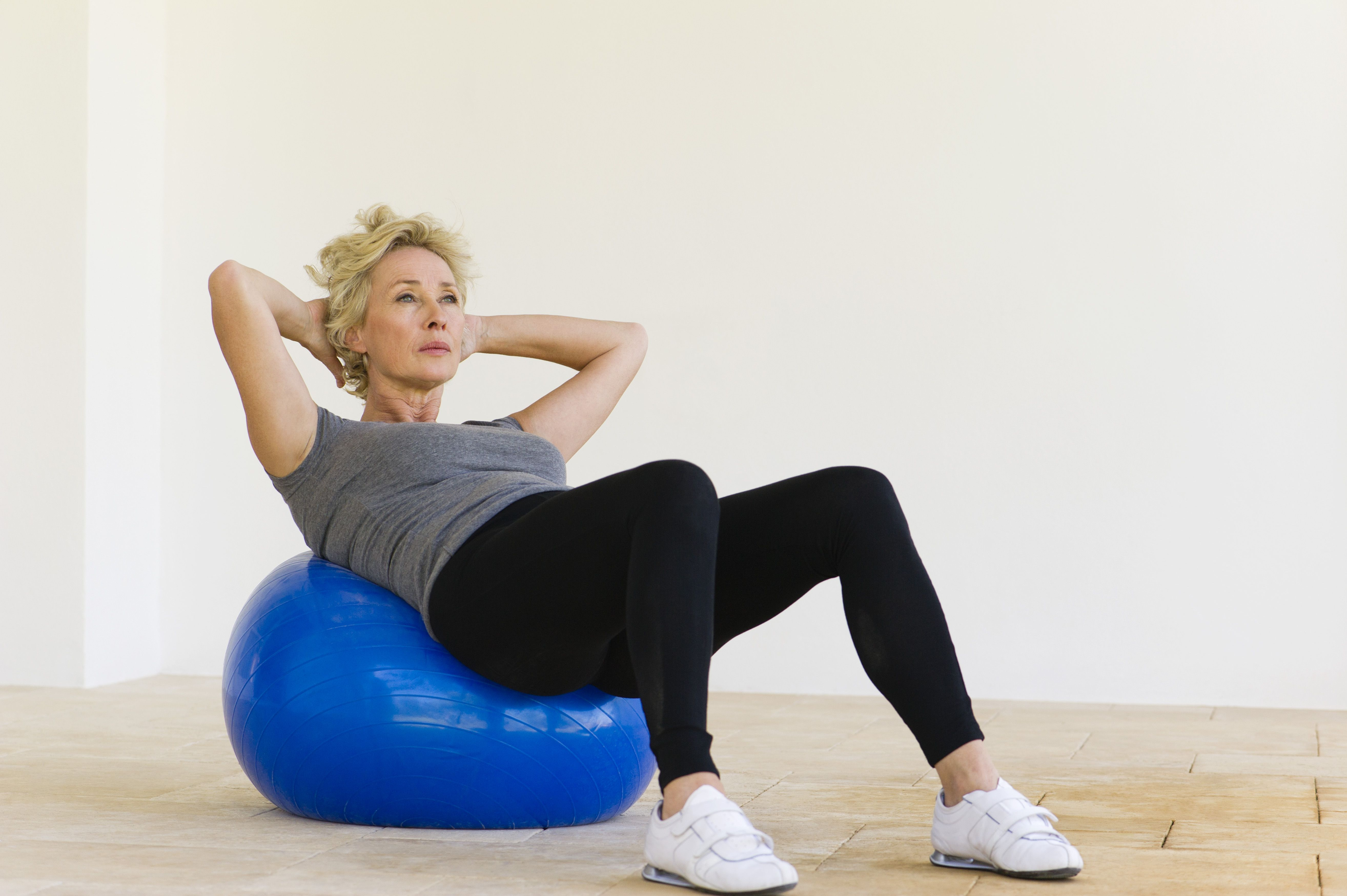 Mature woman doing sit-ups on fitness ball