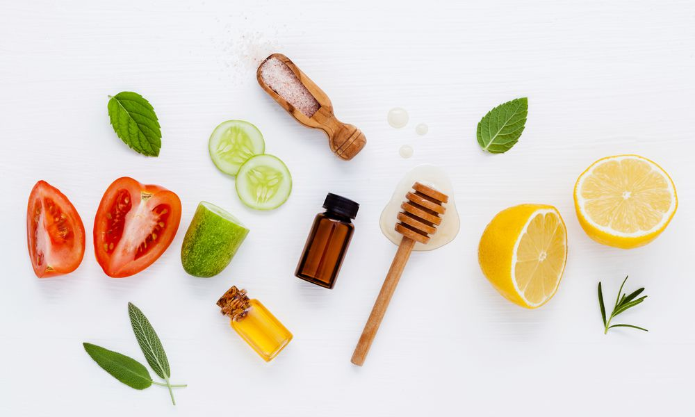 High angle view of essential oil, honey, lemon and other ingredients on white background