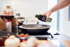 Close-up of male hand pouring oil into pan in the kitchen