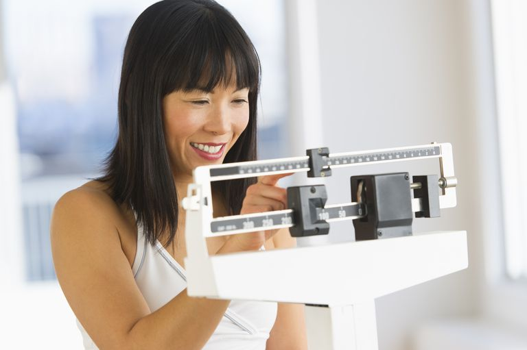 USA, New Jersey, Jersey City, Smiling woman checking her weight
