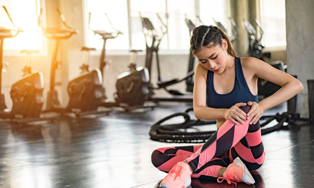 young woman holding knee while sitting on floor in gym