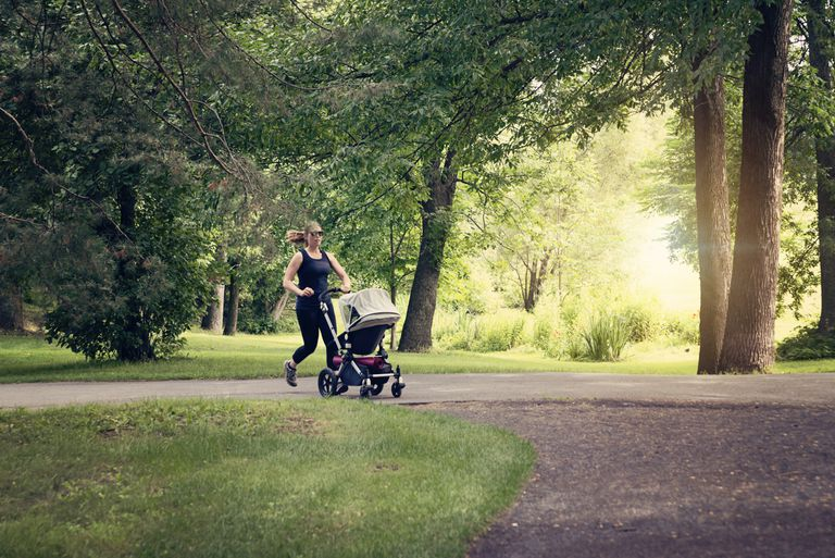 New mother jogging with stroller in public park.
