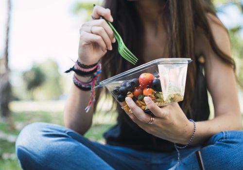 woman eating a salad outside