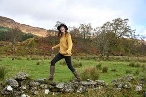 Woman walking along stone wall