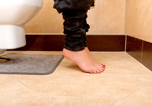 woman's legs shown while on toilet