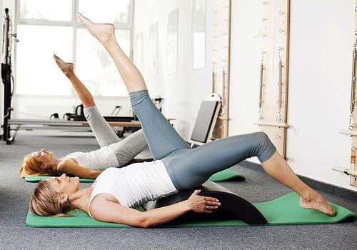 Dos mujeres haciendo pilates en esteras