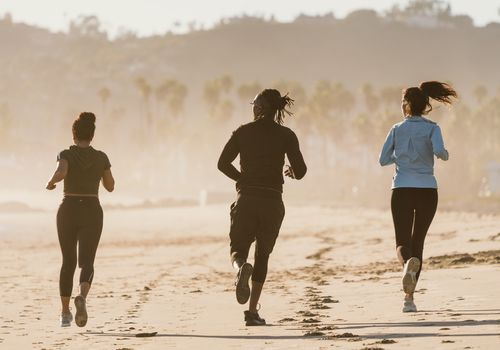 three runners jogging on the beach in the morning