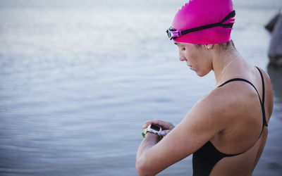 Female open water swimmer checking smart watch at ocean