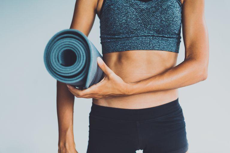 woman holding a pilates mat